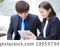 Young Asian business executives in discussion usin 19059794