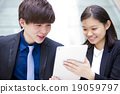 Young Asian business executives in discussion usin 19059797