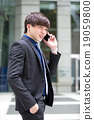 Young Asian male business executive use phone 19059800