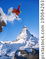 Snowboarder jumping against Matterhorn peak  19064263