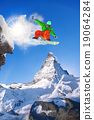 Snowboarder jumping against Matterhorn peak  19064284