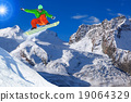 Snowboarder jumping against blue sky 19064329