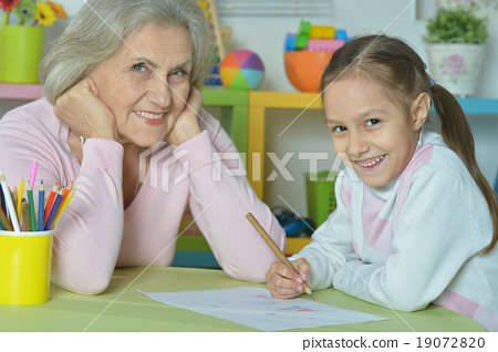 Grandmother with granddaughter drawing together 19072820