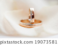 Golden wedding rings with diamonds lie on fabric. 19073581