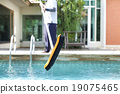 Mna is cleaning a swimming pool with a brush 19075465