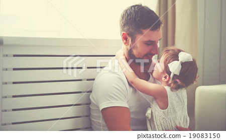 Stock Photo: happy family child baby girl in arms of his father at home