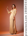 Elegant Woman in Golden Dress with wineglass 19084593