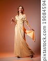 Elegant Woman in Golden Dress with wineglass 19084594