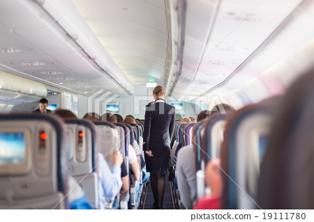 Stock Photo: Stewardess and passengers on commercial airplane.