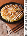 Japanese okonomiyaki on a table close-up 19136418