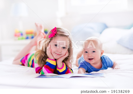 Stock Photo: Kids reading in white bedroom