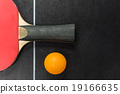 table tennis racket with ball on black table 19166635