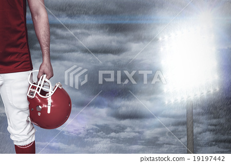 Composite image of american football player holding an helmet 19197442