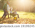 Young parents holding their children in a wheelbarrow 19199245