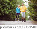 Happy couple roller blading together 19199500