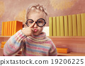 Little girl in glasses makes faces 19206225