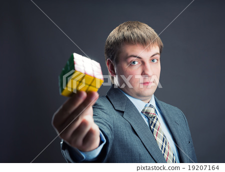 Businessman holding rubik cube in his hands 19207164