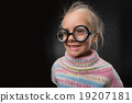 Little girl in glasses makes faces 19207181
