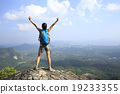 young woman cheering open arms at mountain peak 19233355