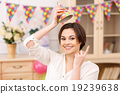 Young smiling girl tries on her party hat 19239638