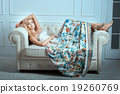 Blonde girl lies on a white sofa. 19260769