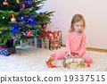 A girl unwrapping presents on Christmas morning 19337515