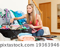 woman putting things in an open suitcase 19363946