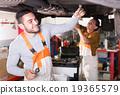 Mechanics repairing car from bottom 19365579