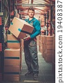 Porter carrying boxes in a warehouse 19408387