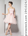 young beautiful brunette in pink dress on white 19410292