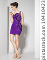 young beautiful brunette in purple dress on white 19410423
