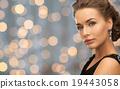 beautiful woman wearing earrings over lights 19443058