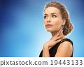 beautiful woman wearing earrings over blue 19443133