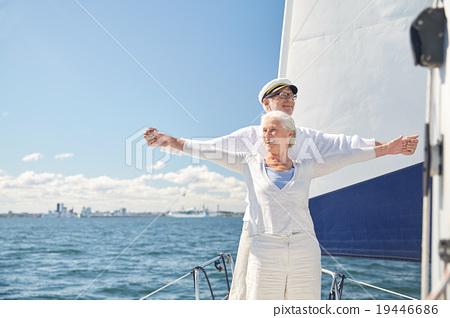 Stock Photo: senior couple enjoying freedom on sail boat in sea