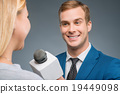 Smiling newsman taking an interview.  19449098