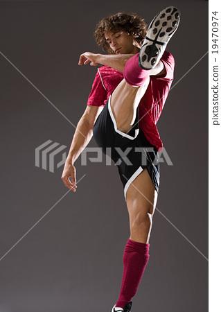 footballer, gray background, kicking 19470974