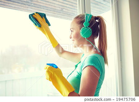 Stock Photo: happy woman with headphones cleaning window
