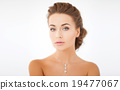 woman wearing shiny diamond pendant 19477067