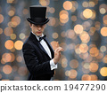 magician in top hat pointing finger up 19477290