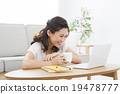 หญิงสาวที่ใช้คอมพิวเตอร์กับโซฟา 19478777