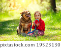 Happy little girl with big dog sitting in the lawn 19523130