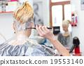 Hairdresser salon. Woman during hair dye.  19553140