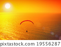 Silhouette of paraglider soaring at sunset 19556287