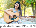 Woman playing guitar. 19590070