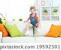 happy child girl playing and jumping on couch at home 19592301