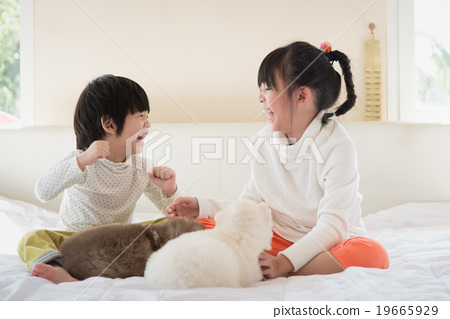 Stock Photo: asian children kissing puppy on white bed