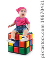Cute female toddler sitting on a colorful cube 19670431
