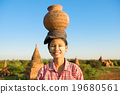 Young Asian traditional female farmer carrying clay pot on head 19680561