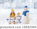 girl plaing with a snowman 19682064