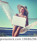 Beautiful Woman Sitting on a Hammock by the Beach Concept 19686296